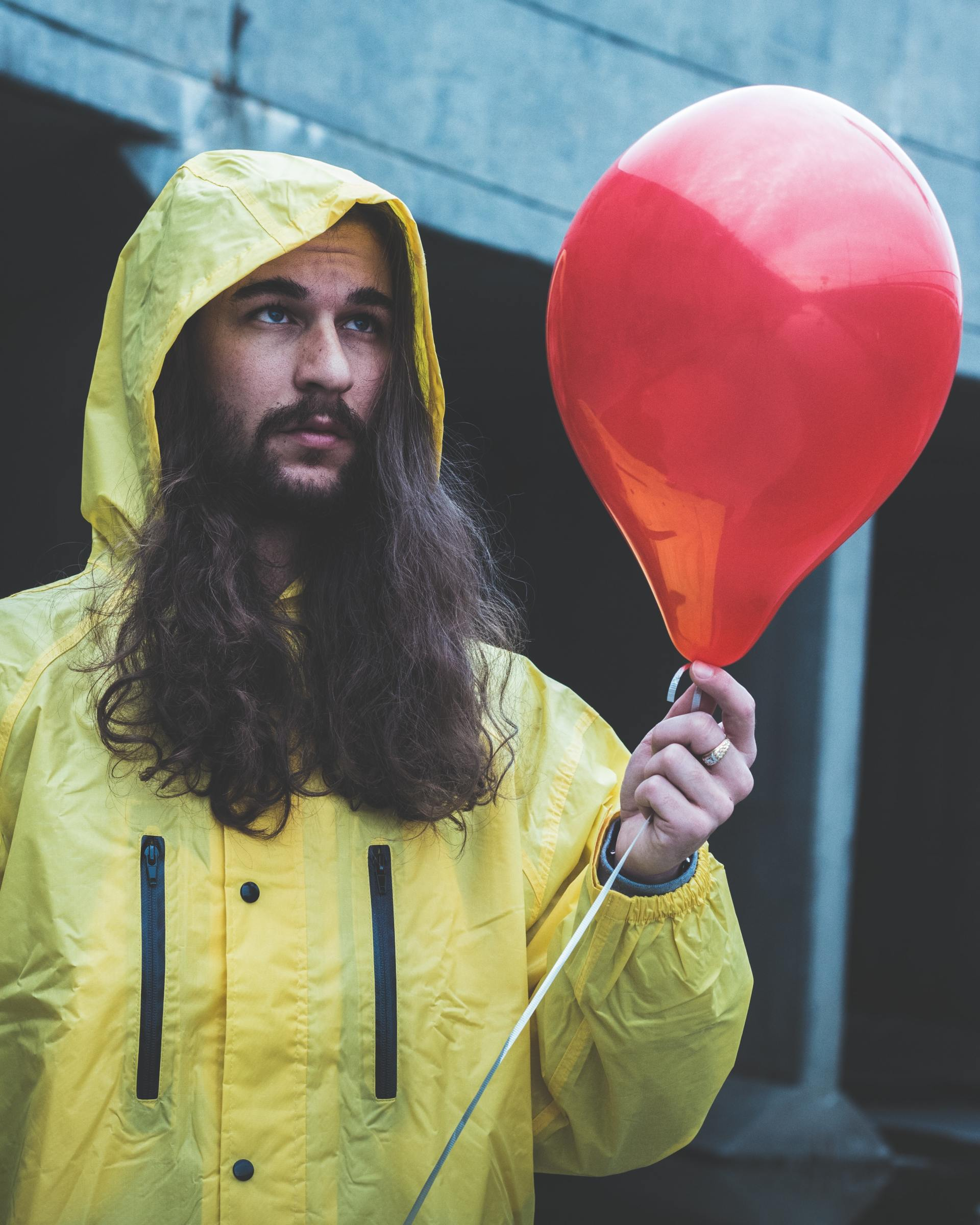 A man with long dark hair and a moustache wears a yellow rain jacket and holds a red balloon