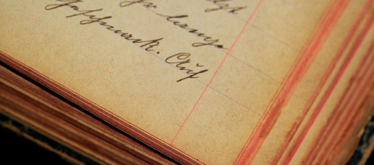 Corner of an old lined notebook with cursive handwriting in ink