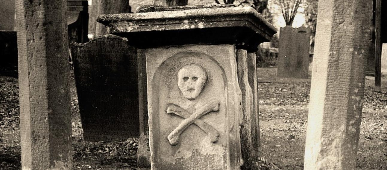Sepia photo of skull and cross bones on a grave in Eyam Village church