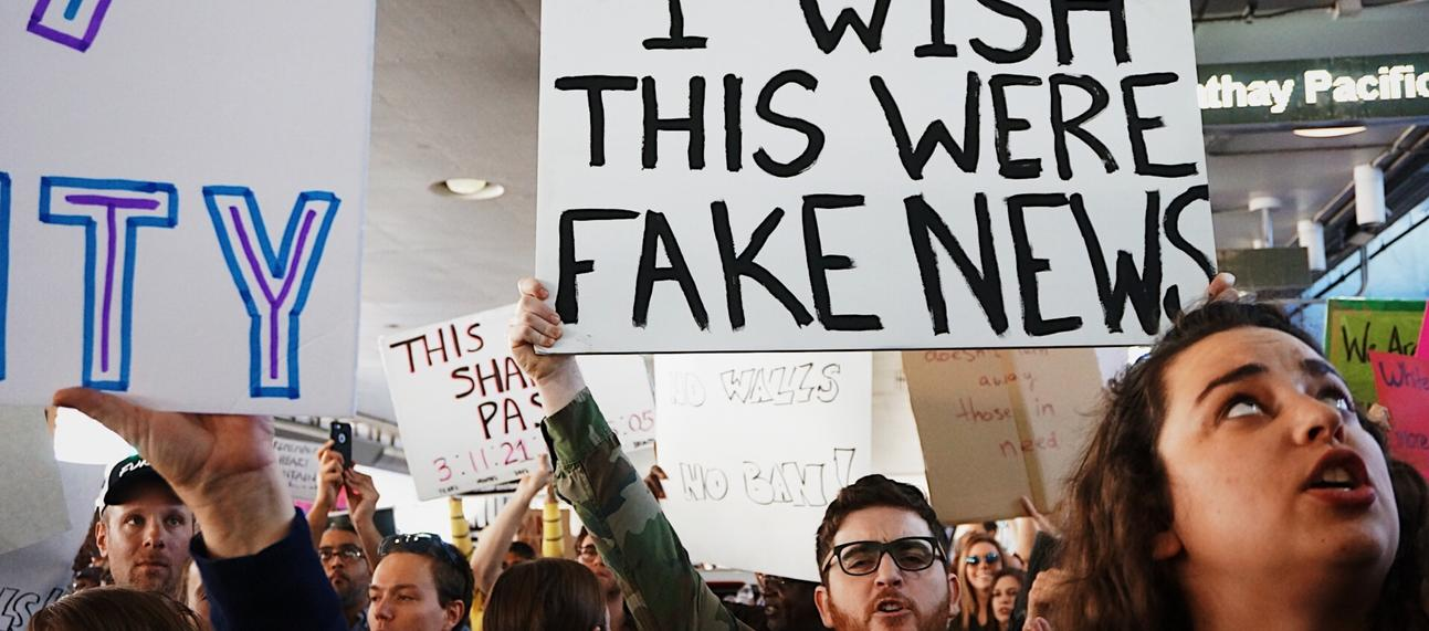 Protest with a man holding a placard that says 'I wish this were fake news'