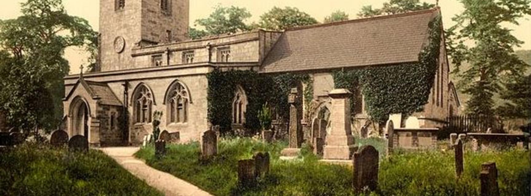 An old postcard of Eyam church and graveyad