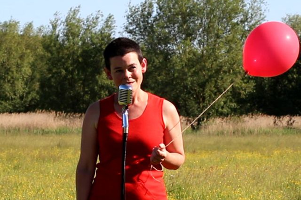 Anna Tolputt speaks into a condenser microphone in a field. She wears a red dress and holds a red balloon.