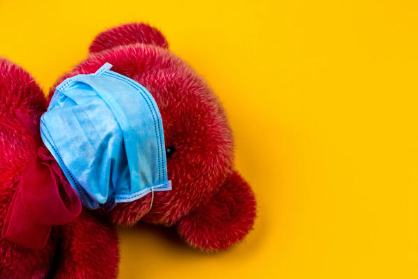 Red teddy bear wearing a blue facemask on a yellow background